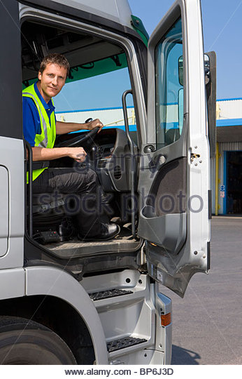 Truck driver sitting in cab of semi-truck - Stock Image