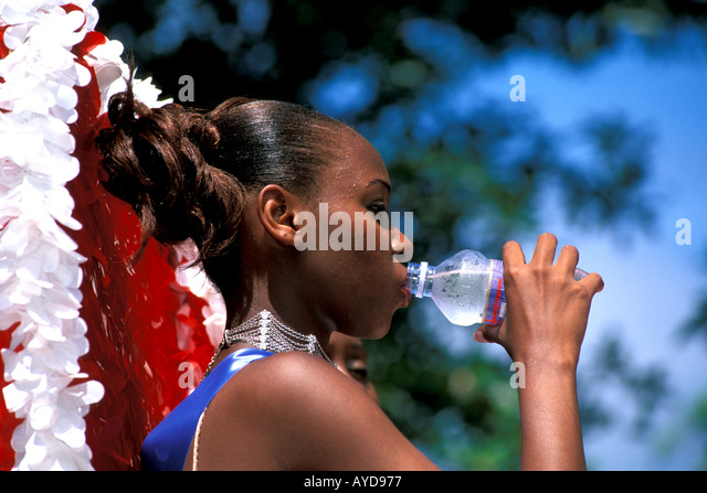 Caribbean Carnival Woman on Float Drinking Water - Stock Image