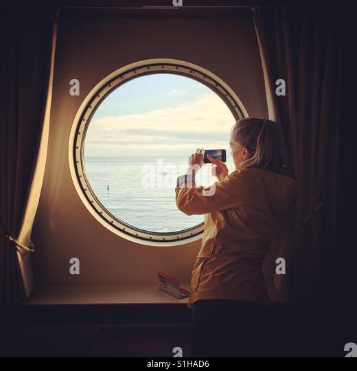 Woman taking photo out of ship window - Stock-Bilder