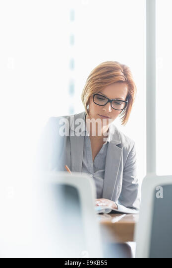 Young businesswoman writing at desk in office - Stock Image