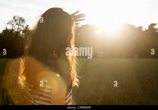 Woman shielding her eyes from sun - Stock Image