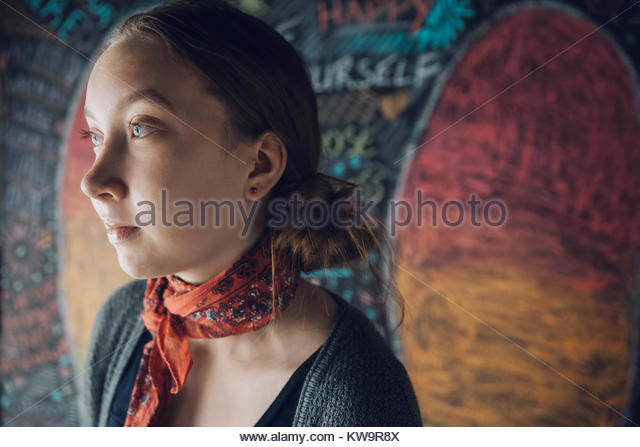Serious,pensive Caucasian tween girl looking away against wall with chalk - Stock Image