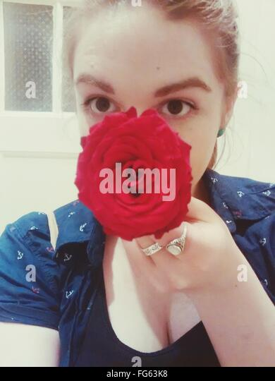 Young Woman Holding Red Rose - Stock Image