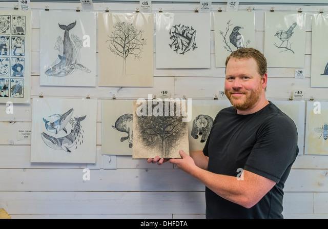 Artist Graham Blair, a woodblock printmaker holds an inked woodblock at his studio in Quidi Vidi in St. John's - Stock Image