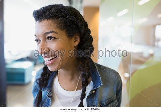 Smiling businesswoman looking away - Stock Image