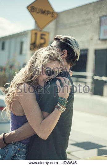 Young couple embracing in street - Stock-Bilder
