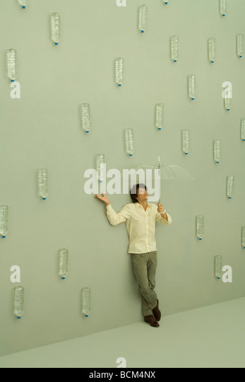 Man holding umbrella, water bottles falling like raindrops around him - Stock Image