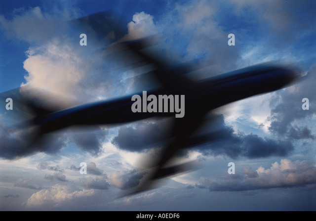 blurred silhouette of plane against sky - Stock Image