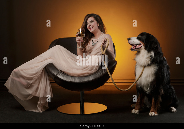 Woman drinking a glass of wine alongside huge dog - Stock Image