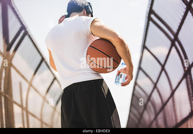 Rear view of young male basketball player walking along footbridge listening to headphones - Stock Image