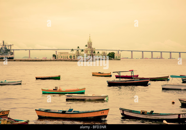 colorful boats and fort on harbor in Rio overlooking South Americas longest bridge - Stock Image