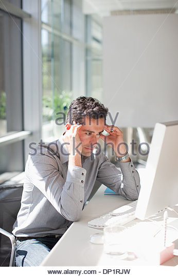Businessman looking at computer with head in hands - Stock-Bilder