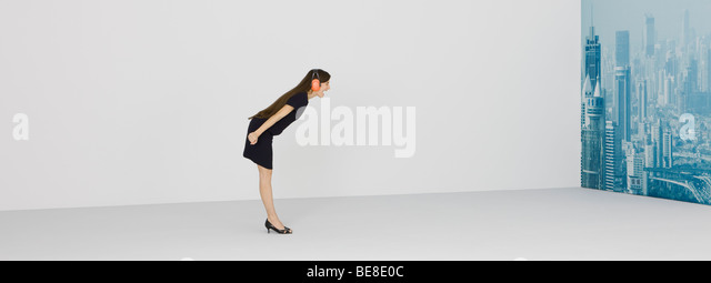 Woman wearing protective headphones, shouting at cityscape - Stock Image