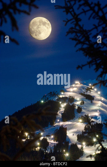 Winter moonrise over Mt. Alyeska during the annual Torchlight Parade, Girdwood, Southcentral Alaska, Winter, COMPOSITE - Stock Image