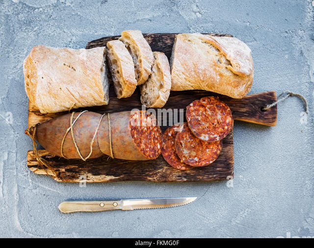 Wine snack set. Hungarian mangalica pork salami sausage and rustic bread on dark wooden board over a rough grey - Stock Image