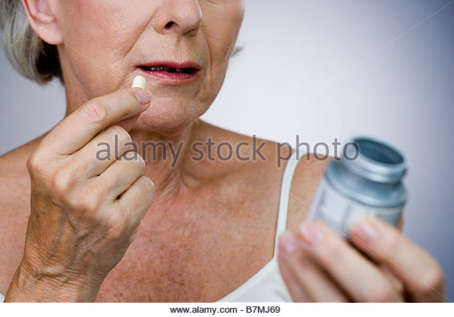 A senior woman holding a bottle of pills - Stock Image