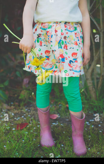 Low section of a girl holding dandelion flowers - Stock Image