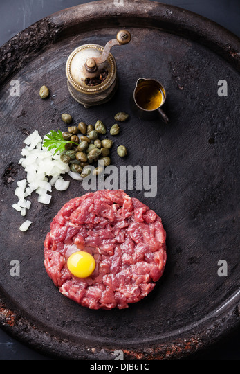 Beef tartar with capers and fresh onions on black textured background - Stock Image