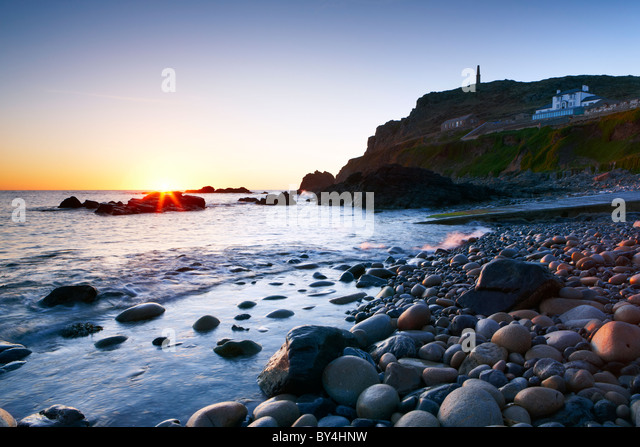 A clear evening sky and the last rays of sunlight highlight the small rocky beach at Priest's Cove Cape Cornwall - Stock Image