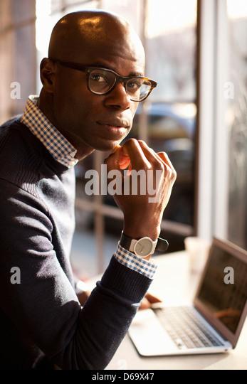 Businessman using laptop in cafe - Stock-Bilder