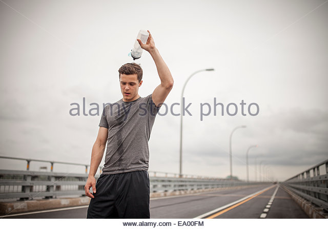 Young man pouring water over head - Stock-Bilder