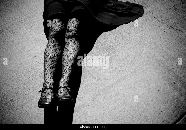 Woman wearing tights, laying on pavement. Black and white. - Stock Image