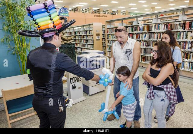 Miami Florida Hialeah JFK Library Health and Literacy Fair interior Hispanic man balloon artist twister modeling - Stock Image
