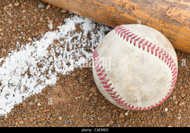 An old worn baseball and bat on a baseball field - Stock Image