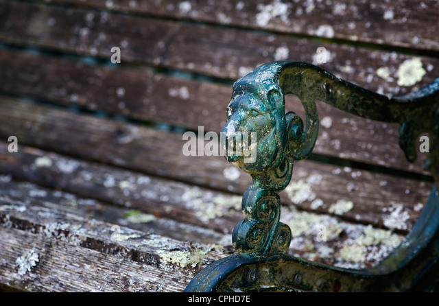 Old rustic garden seat with a lions head arm rest - Stock Image