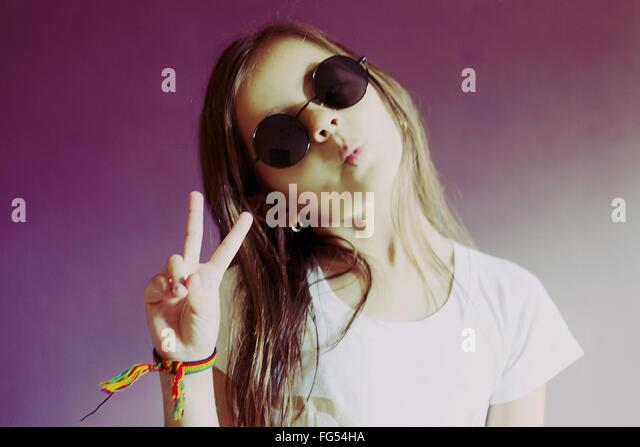 Portrait Of Girl In Retro Sunglasses Gesturing Peace Sign Against Wall At Home - Stock-Bilder