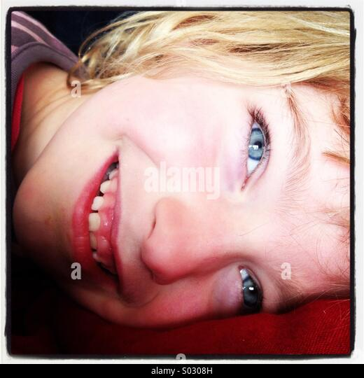 A smiling joyously happy girl with blue eyes lying down... - Stock-Bilder