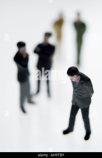 Downcast man ignored by figures in the background - Stock Image