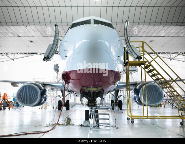 Airplane docked in hangar - Stock Image