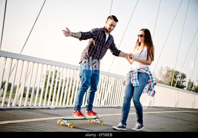 Young man balancing on skateboard, woman assisting - Stock Image