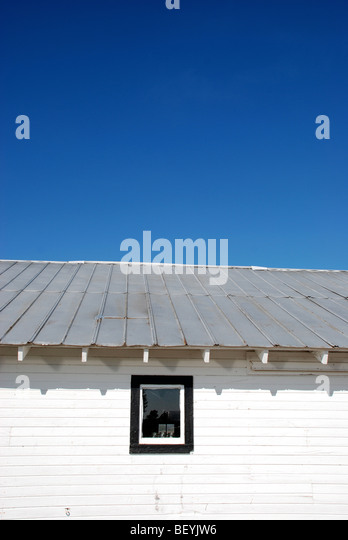 White barn under blue skies - Stock Image