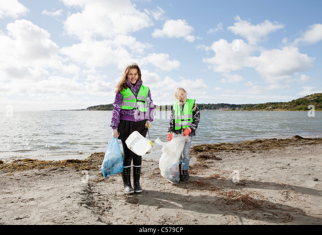 Girls in safety vests cleaning beach - Stock Image