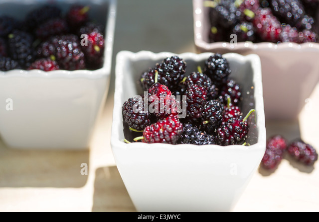 ceramic pots filled with Spanish grown mulberries on wooden table - Stock Image
