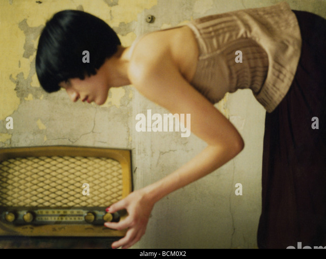 Woman bending over, turning dial on old fashioned radio - Stock Image