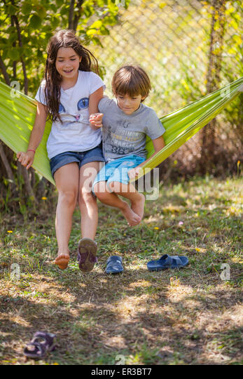 Boy and girl sitting on a hammock  in the garden - Stock Image