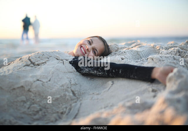 Beach, joy and fun. Laughing, happy girl lying on a sandy beach - Stock Image