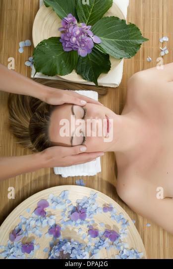 Woman lying down having head massage - Stock Image