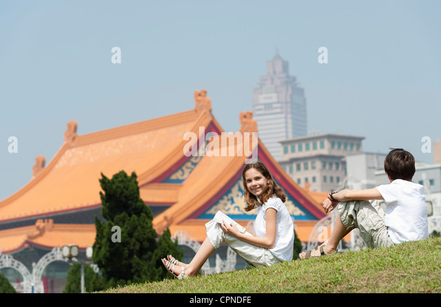 Girl sitting on grass with brother near National Concert Hall, Chiang Kai-Shek Memorial Hall, Taipei, Taiwan - Stock Image