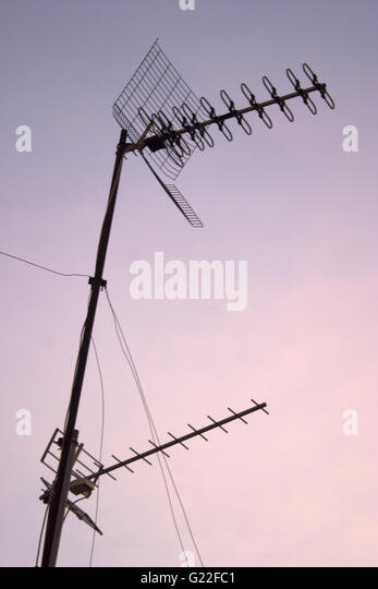 a poetic picture of television aerials on rooftop with cloudy pink and blue sky at sunset, detail, Palma de Mallorca, - Stock Image