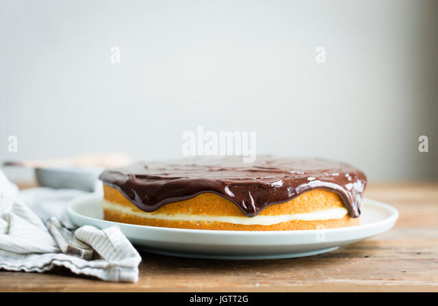 Vanilla layer cake with cream filling and chocolate sauce topping - Stock Image