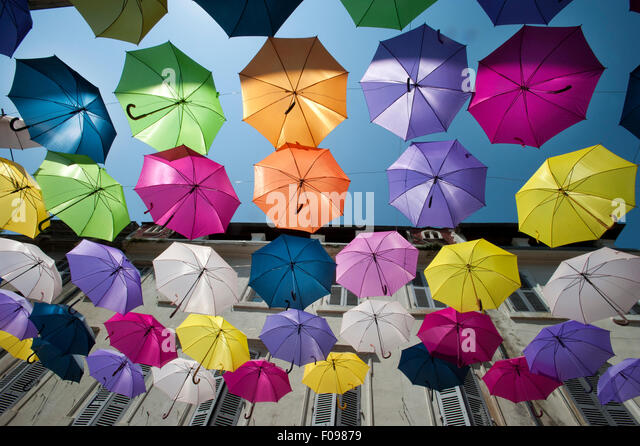Brightly coloured floating umbrellas fill the sky above Rue Jean Jaures, Arles,Bouches-du-Rhône department, - Stock Image
