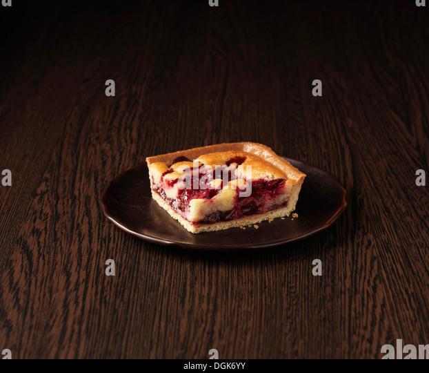 Slice of morello cherry frangipane tart - Stock-Bilder