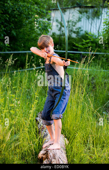 Boy shooting a bow and arrow - Stock Image