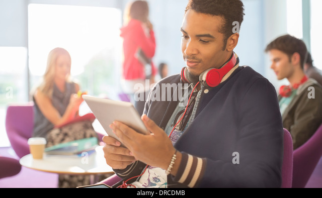 University student using digital tablet in lounge - Stock Image