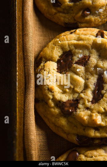 Chocolate Chip Cookies on a Wood Tray over a brown linen napkin. - Stock Image
