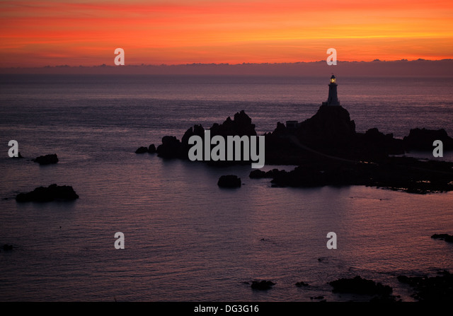 Corbiere Point and Lighthouse. St. Brelade. SW. Jersey, Channel Islands. UK. August evening sunset. - Stock Image